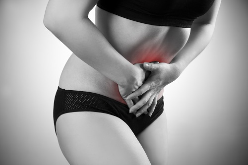 Woman with abdominal pain. Pain in the  human body. Black and white photo with red dot